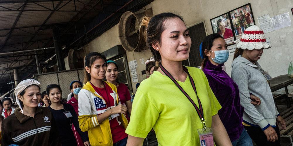 Kuvassa ryhmä kambodzalaisen tehtaan naistyöntekijöitä kävelee tauolla töistään